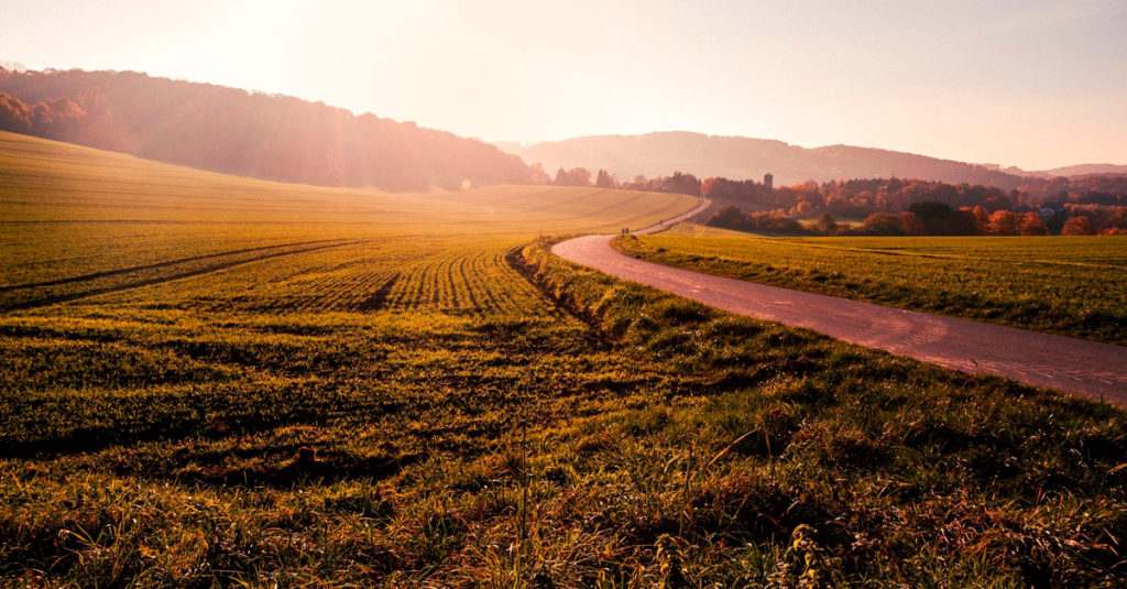 Image of sunrise over rural road, fields and hills