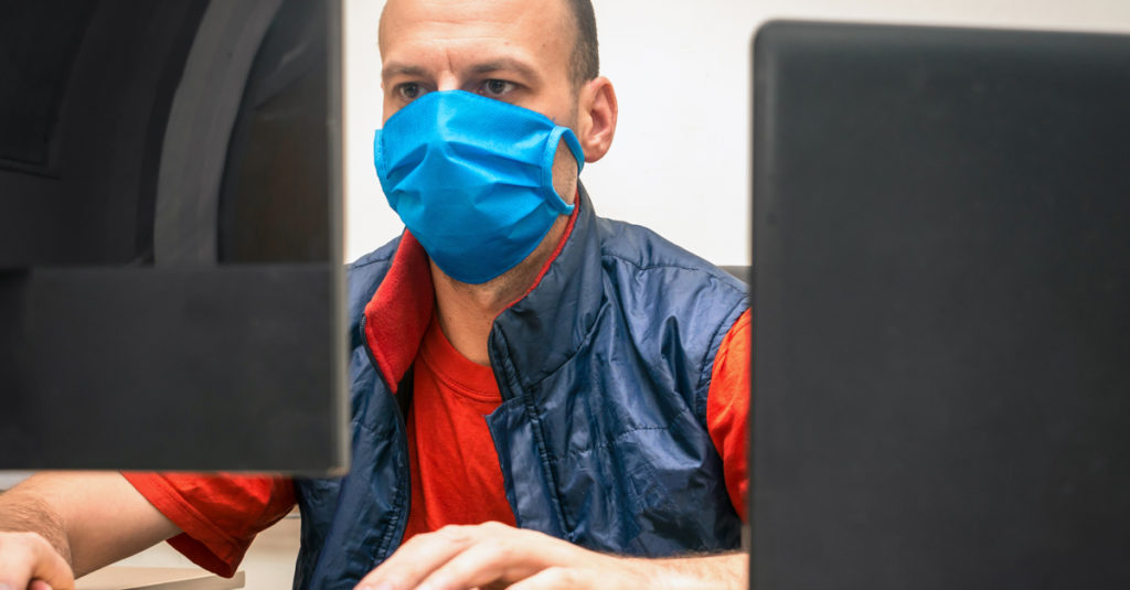 Man in medical mask sitting in front of monitor screens